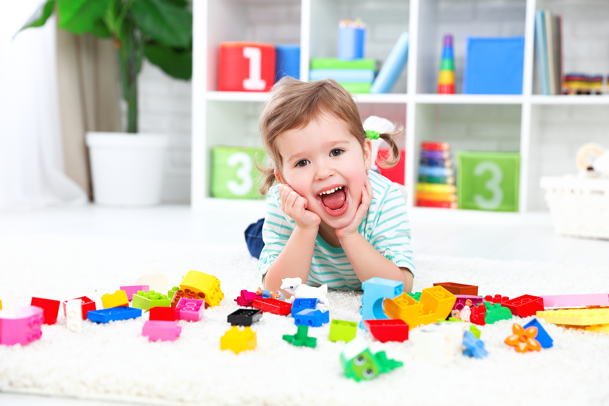 happy child girl laughing and playing with toys constructor