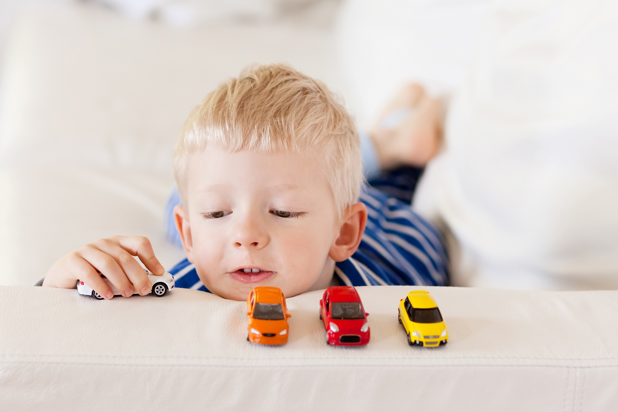 young caucasian boy plays with colorful toy cars