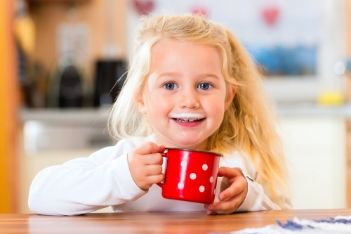 child drinking cup or mug of milk in the domestic kitchen