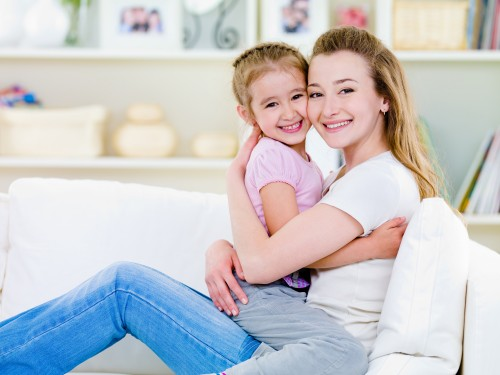 Happiness of mother with little daughter sitting together in embrase on the sofa - indoors