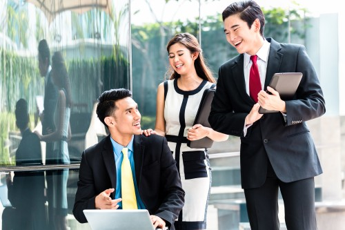 Asian businesspeople working outside on laptop